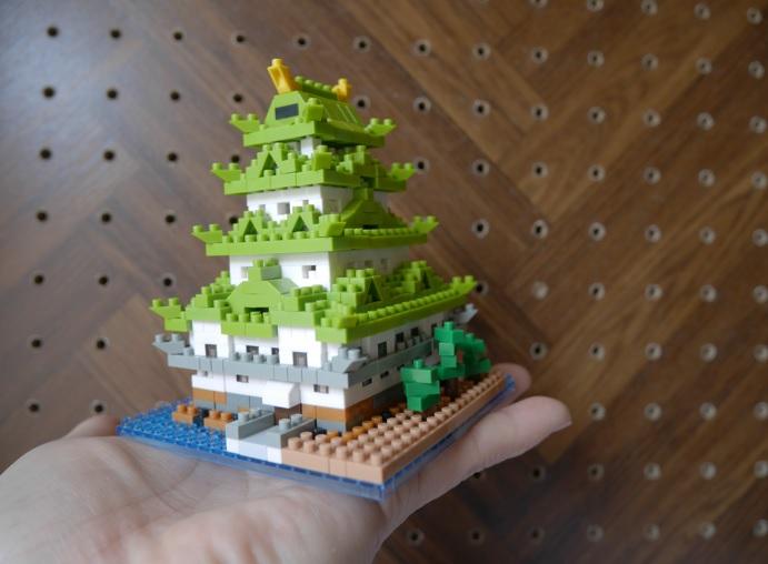 ナノブロックの名古屋城を手にのせているところ