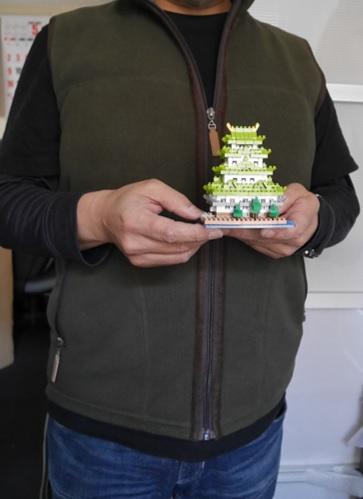 ナノブロックの名古屋城を手にもっている男性