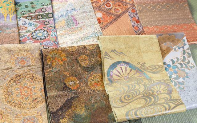 着物の帯がたくさん畳の上に並んでいるところ